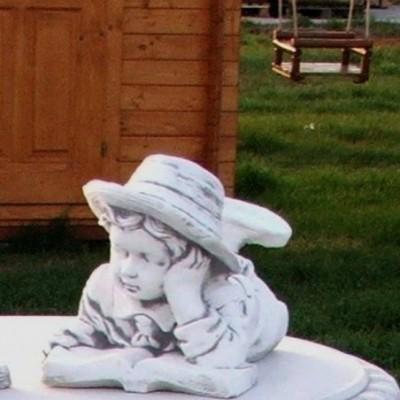 Kerti figura fekvő könyves fiú